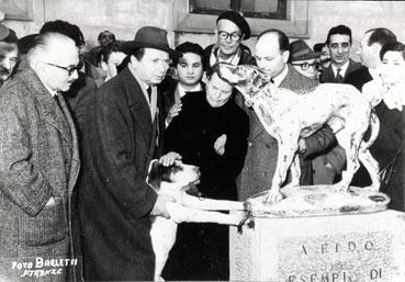 Il giorno dell'inaugurazione del monumento in piazza Dante; Fido con la vedova Soriani in basso attorniato da tanta gente.(Foto Barletti)