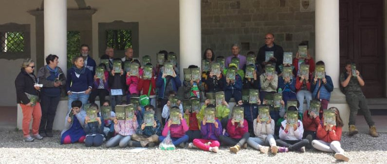 Classi della scuola primaria di Scarperia dopo l'escursione nel bosco mostrano il libro fumetto che accompagna il progetto didattico.