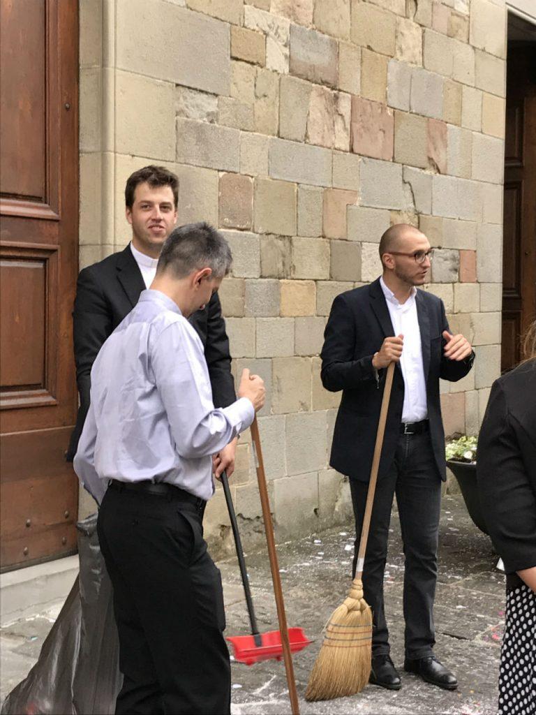 I tre sacerdoti, dopo aver celebrato il matrimonio di Caterina e Paolo, eccoli a spazzare il sagrato della chiesa, pieno di festoni e cuoricini di carta